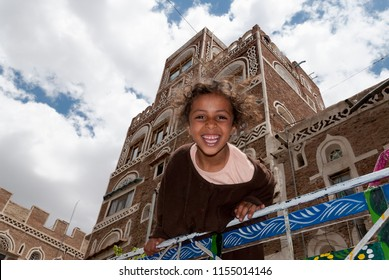 Sanaa, Yemen - May 4, 2007: A girl on a vehicle smiles at the camera. Although infant mortality is high, children in Yemen are culturally, socially and religiously valued.