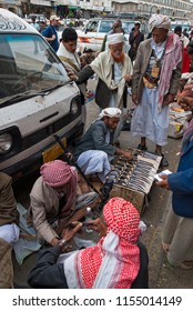Sanaa, Yemen - May 4, 2007: Men in traditional clothes buy  janbiyas. Janbiya is a traditional knife that yemeni men wear it as an accessory to their clothing.