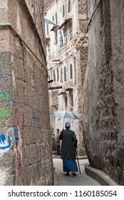 Sanaa, Yemen - May 4, 2007: An old man with an umbrella walks in the narrow streets of Sanaa. The Old City of Sanaa is a UNESCO World Heritage City.