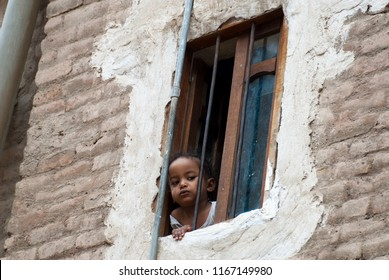 Sanaa, Yemen - May 4, 2007: A little girl looks behind the bars of her window. Although infant mortality is high, children in Yemen are culturally, socially and religiously valued.
