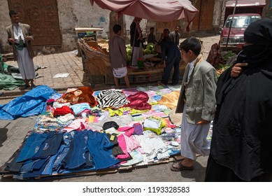 Sanaa, Yemen - May 4, 2007: A woman dressed in black and her son buy clothes in an open market. Open markets play a central role in the social-economic life of Yemen.