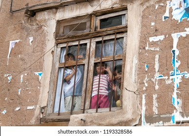 Sanaa, Yemen - May 4, 2007: Three happy boys laugh and wave with their hands behind the bars of a window. Although infant mortality is high, children in Yemen are culturally and socially valued.