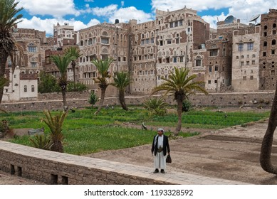 Sanaa, Yemen - May 4, 2007: A man in traditional clothes stands in front of multi-storey buildings made of stone. The Old City of Sanaa is a UNESCO World Heritage City.