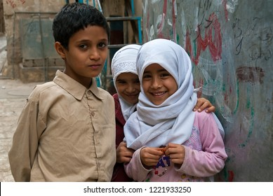 Sanaa, Yemen - May 4, 2007: Two girls and a boy pose smiling to the camera. Although infant mortality is high, children in Yemen are socially valued.