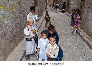 Sanaa, Yemen - May 4, 2007: A group of boys pose to the camera in a narrow street.