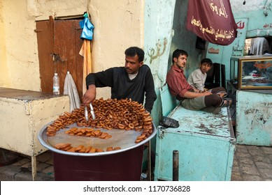 Sanaa, Yemen - May 5, 2007: A man sells donuts in an open market. Open markets play a central role in the social-economic life of Yemen.