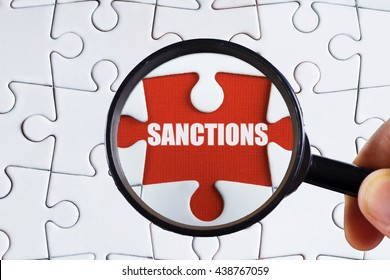"""Sanctions"" text on red missing jigsaw puzzle with man right hand hold black magnifying glass searching for missing puzzle peace - business and finance concept"