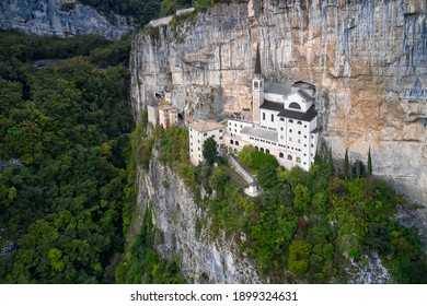 The sanctuary is high in the mountains of Italy. The unique Sanctuary Madonna della Corona church was built in the rock. Aerial view of the church on the sheer cliff. Italian church in the Alps.