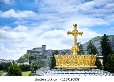 Sanctuary of Lourdes. Dome of The Basilica of Our Lady of the Rosary. The Golden Crown and the Cross. Blue sky with clouds. Hautes-Pyrenees department in the Occitanie region in south-western France