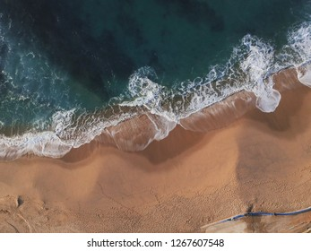 Sand beach aerial, top view of a beautiful sandy beach aerial shot with the blue ocean water