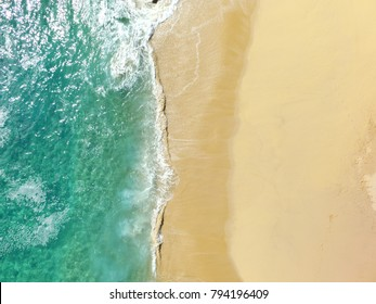 Sand beach aerial, top view of a beautiful sandy beach aerial shot with the blue waves rolling into the shore, some rocks present