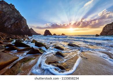 Sand beach among rocks on evening sunset. Ursa Beach near Cape Roca (Cabo da Roca) at Atlantic Ocean coast in Portugal. Summer landscape.
