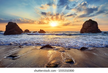 Sand beach among rocks on evening sunset. Ursa Beach near Cape Roca (Cabo da Roca) at Atlantic Ocean coast in Portugal. Summer landscape.