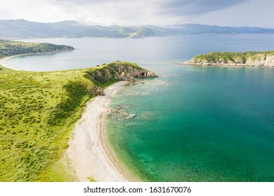 Sand beach in beautiful bay with turquoise sea water. Aerial view of Cape Vkhodnoy at Gamov Peninsula in sunny summer weather. Seaside nature landscape in Primorsky Krai, Far East, Russia