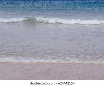 Sand beach and blue ocean in Scotland with waves.
