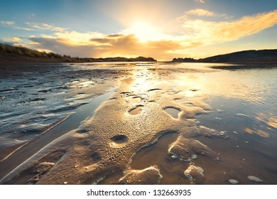 sand beach by North sea at low tide during sunset