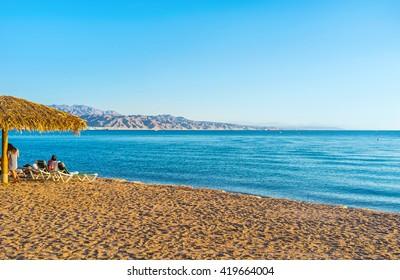 The sand beach in Eilat with the scenic Aqaba mountains on the background, Eilat, Israel.
