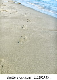 Sand beach and footprints near sea wave