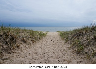 Sand with beach grass in foreground, cloudy sky, lake in background