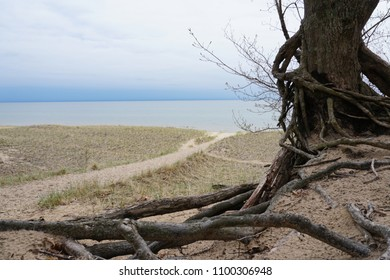 Sand, beach grass and path to lake, cloudy sky with lake in background