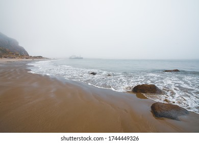 Sand beach and Morro Rock on overcast day, California