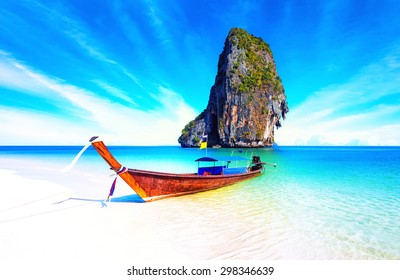 Sand beach on sea coast of tropical island in Thailand at sunny summer day with blue sky and clear water. Holiday vacation background