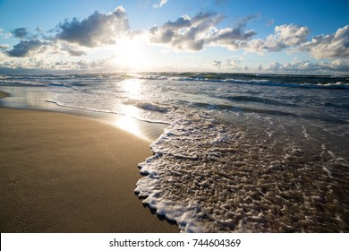 Sand beach and sea waves, Baltic sea seashore during sunset. Curonian spit, Kaliningrad region, Russia