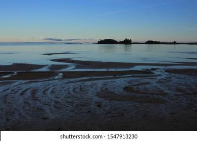 Sand beach and small island in Vita Sannar, Sweden. Evening scene at the shore of Lake Vanern.