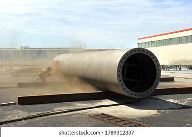 Sand blasting process, Industial worker using sand blasting process preparation cleaning surface on steel before painting in factory workshop