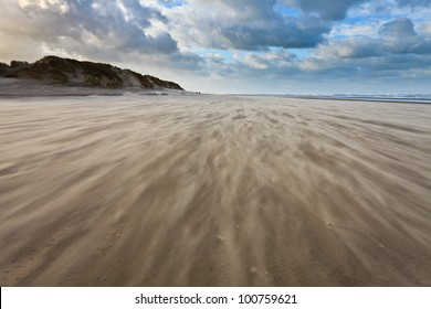 Sand blowing over the beach near the sea