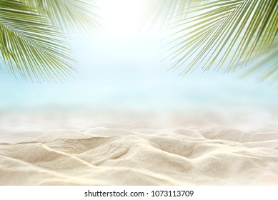 Sand with blurred Palm and tropical beach and sea background, Summer vacation and travel concept. Copy space