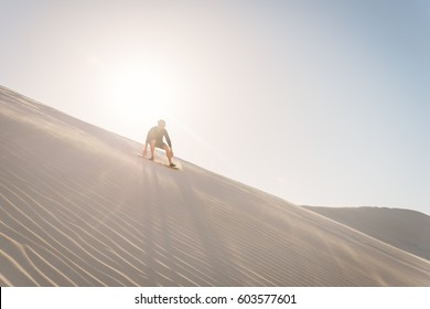 Sand boarding backpackers at the Lancelin sand dunes near Perth, Western Australia