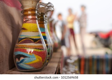 Sand bottles souvenirs in a market shop, tourists in the background