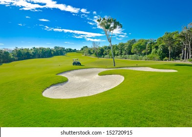 Sand bunker on the beautiful golf course with the golf cart at the back. Mexican resort. Bahia Principe.  Riviera Maya.