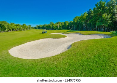 Sand bunker on the beautiful golf course with the golf cart at the back. Mexican resort.