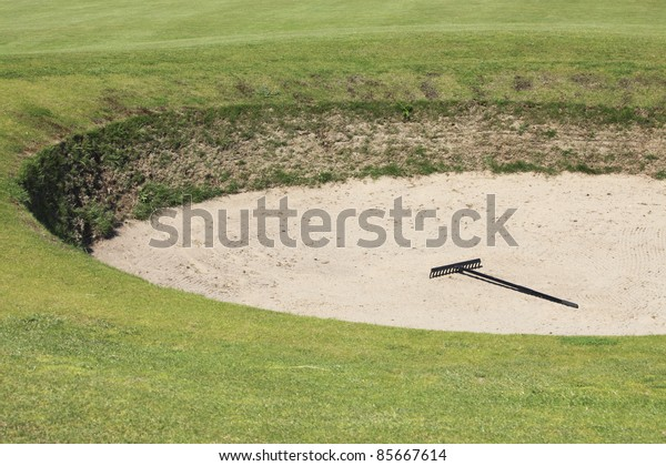 Sand bunker on the golf course with a rake lying in the middle
