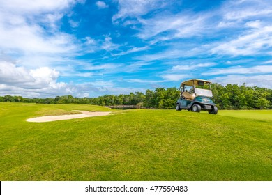 Sand bunkers and a golf cart at the golf course.