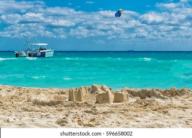 Sand castle build on a mexican beach in front of turquoise water and a lot of water sport activities, acting as an advertising for summer holiday.