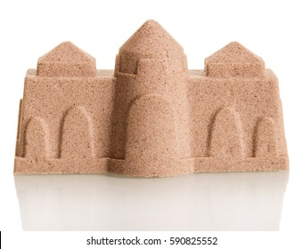 Sand castle close-up isolated on white background.