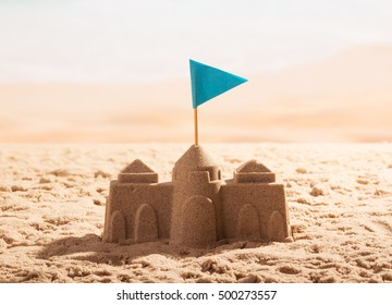 Sand castle with a flag on the sea shore.