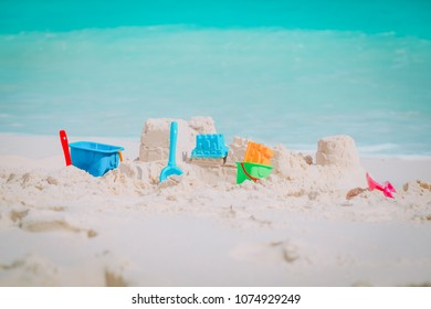 Sand castle on beach and kids toys