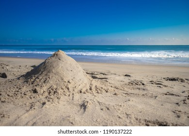 sand castle on white sand beach meet tropical ocean with small waves and nice blue sky background in Summer - Ocean City, Maryland USA
