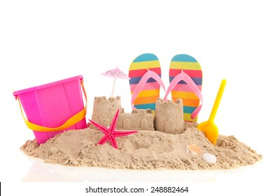 Sand castle and toys at the beach isolated over white background