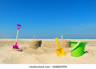Sand castle with toys and shells at the beach