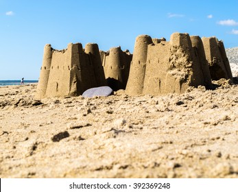 Sand castles found on the beach at Dinas Dinlle in Gwynedd, North Wales UK. It is a sunny day and there is an unrecognisable person and a lightly clouded blue sky in the background.