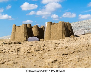 Sand castles found on the beach at Dinas Dinlle in Gwynedd, North Wales UK. It is a sunny day and there is a lightly clouded blue sky in the background.