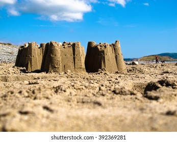 Sand castles on the beach at Aberdesach, North Wales UK in bright sunshine against a blue sky with fluffy white clouds