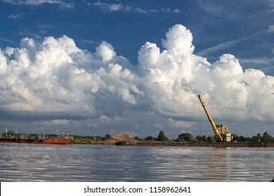 Sand charging on Volga, Russia. Boat, crane and beautiful cloudy sky