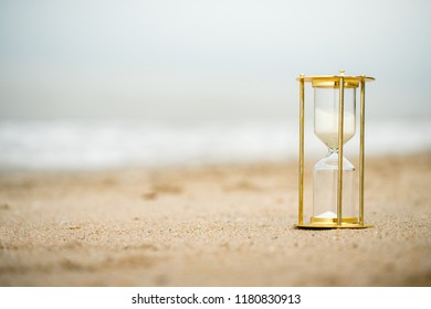 Sand clock on the beach, business time management concept