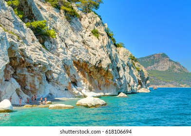 Sand color stone rocks beach with green trees in the Mediterranean Sea Turkey seaside. Swimming people tourists. Best Turkey holidays vacations famous boat tours on Mediterranean Sea. Romantic beach